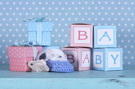Photo pour Baby nursery bootie, dummy pacifier and baby letters pink and blue gift boxes against a vintage aqua blue table and polka dot background for baby shower or newborn girl greeting card  - image libre de droit