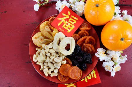 Photo for Happy Chinese New Year celebration party tray of togetherness on red wood background. - Royalty Free Image