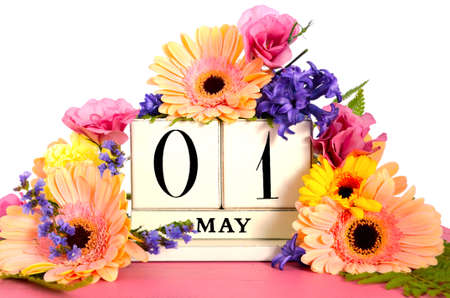 Photo pour Happy May Day vintage wood calendar decorated with Spring flowers on pink wood table. - image libre de droit