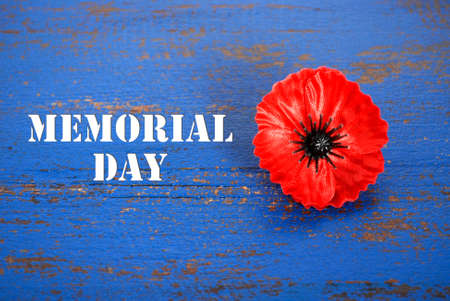 Photo for USA Memorial Day concept of red remembrance poppy on dark blue vintage distressed wood table, with title text. - Royalty Free Image
