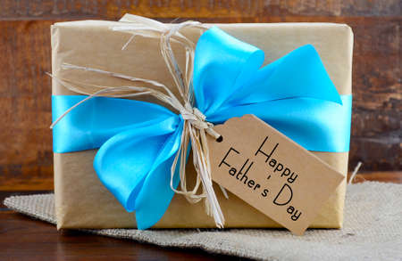 Photo pour Happy Fathers Day natural kraft paper wrapped gift owith pale blue ribbon on dark wood background. - image libre de droit
