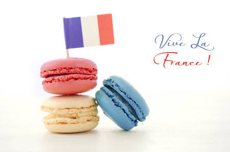 Photo pour Happy Bastille Day red, white and blue macarons with French flag on white wood table with Vive La France sample text. - image libre de droit