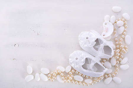 Photo for Baby shower neutral white background with baby booties, pearls, and sugar almonds on shabby chic rustic wood table, with copy space. - Royalty Free Image