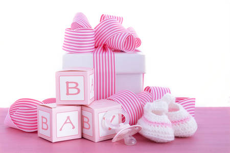 Photo pour Baby shower Its a Girl pink gift with baby booties, dummy and gift box on pink shabby chic wood table. - image libre de droit