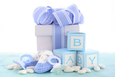 Photo pour Baby shower Its a Boy blue gift, with gift box, baby booties and dummy on pale blue shabby chic rustic wood table. - image libre de droit