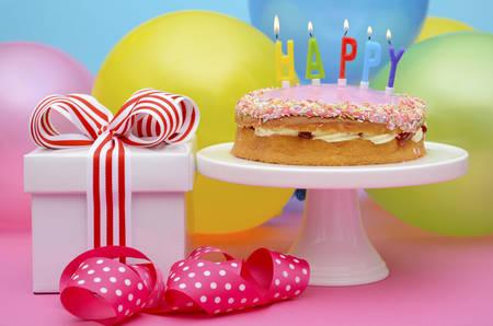 Foto de Bright colorful party table with balloons and gifts with bright color ribbons and bows, and Happy Birthday cake on cake stand. - Imagen libre de derechos