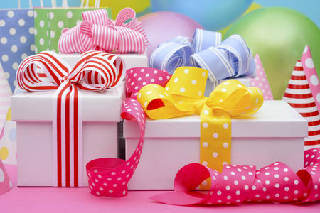 Photo for Bright colorful party table with balloons, streamers, party favor gift bags and gifts with bright color ribbons and bows. - Royalty Free Image