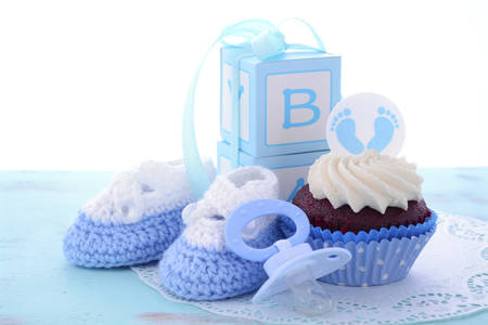 Photo for Its a Boy Blue Baby Shower Cupcakes with baby feet toppers and decorations on shabby chic blue wood table. - Royalty Free Image