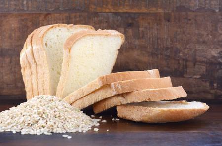 Foto de Gluten free rice sliced sour dough bread with raw brown rice on dark wood table background. - Imagen libre de derechos