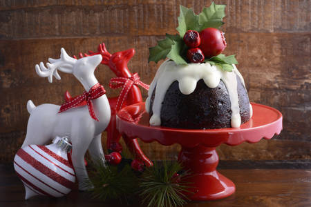 Photo for Traditional Christmas Plum Pudding on red cake stand with reindeer ornaments against a dark wood background. - Royalty Free Image