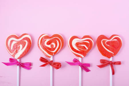 Photo for Happy Valentines Day candy with red heart shape lollipops on pink wood background. - Royalty Free Image