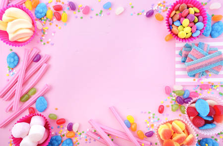 Photo for Background with decorated borders of bright colorful candy on pink wood table for Halloween trick of treat or childrens birthday party favors. - Royalty Free Image