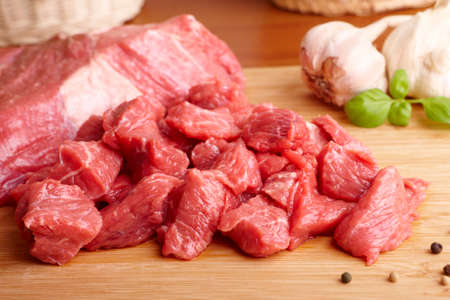 Fresh raw beef on wooden cutting board with garlic, pepper and bazil