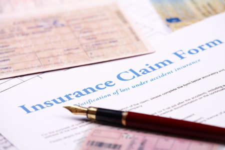 Photo pour Blank insurance claim form and other papers like ID or vehicle documents and pen lying on desk - image libre de droit