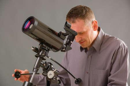 Man looking skyward through astronomical telescope