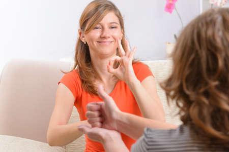 Foto de Smiling deaf woman learning sign language - Imagen libre de derechos