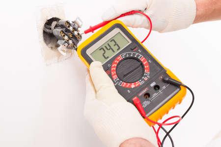 Foto de Electrician checking socket voltage with digital multimeter - Imagen libre de derechos