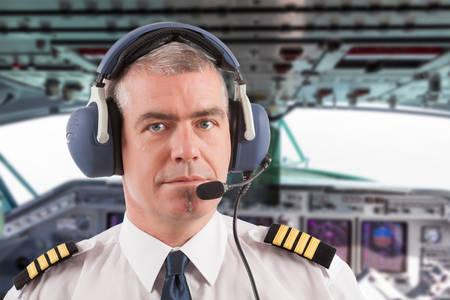 Foto de Airline pilot wearing uniform with epaulettes and headset, on board passenger aircraft. - Imagen libre de derechos