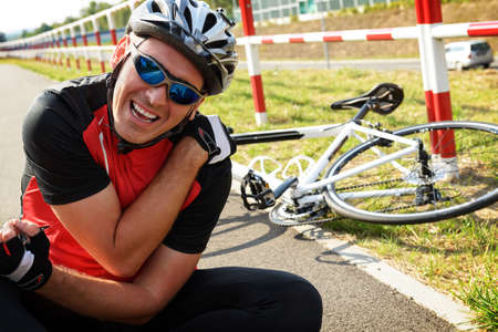 Photo pour Bicycle accident. Biker holding his shoulder. - image libre de droit