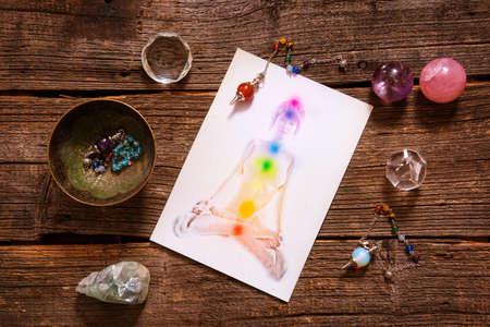 Foto de Chakras illustrated over human body with natural crystals and pendulum - Imagen libre de derechos
