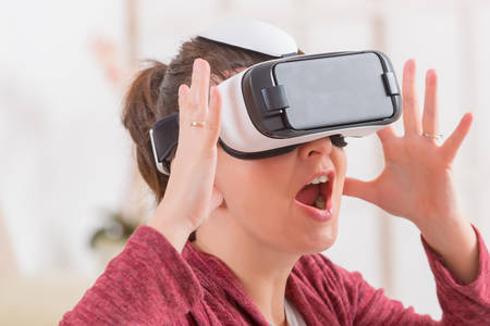 Photo pour Happy woman using virtual reality headset at home - image libre de droit