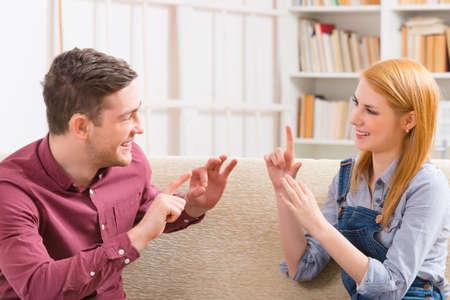 Foto de Smiling young woman talking using sign language with her hearing impairment man - Imagen libre de derechos