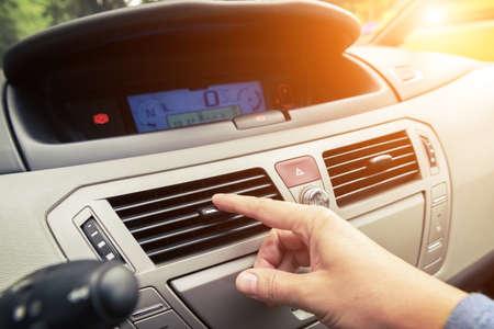 Foto de Driver hand tuning air ventilation grille, emergency flasher switch and light in modern car interior - Imagen libre de derechos