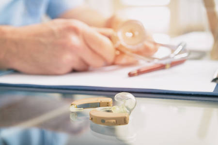 Foto de Doctor audiologist and hearing aid on a table - Imagen libre de derechos