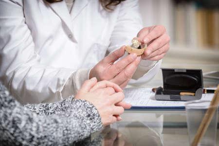 Foto de Doctor showing hearing aid to her patient in the doctor's office - Imagen libre de derechos