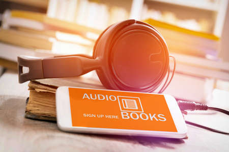 Photo for Smart phone with audio books application on screen, headphones and the paper books. Concept of listening to audiobooks. - Royalty Free Image