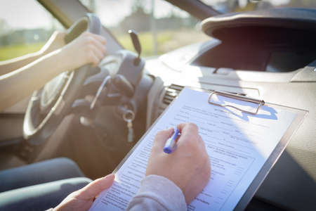 Photo for Examiner filling in driver's license road test form sitting with her student inside a car - Royalty Free Image