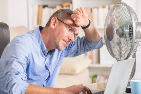 Foto de Man suffers from heat while working in the office and tries to cool off by the fan - Imagen libre de derechos