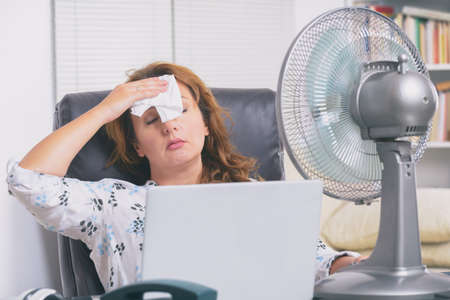 Foto de Woman suffers from heat while working in the office and tries to cool off by the fan - Imagen libre de derechos