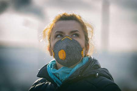 Foto de Woman wearing a real anti-pollution, anti-smog and viruses face mask; dense smog in air. - Imagen libre de derechos