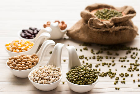collection set of beans, legumes, peas, lentils on ceramic spoons on white wooden background