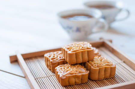 Photo for Retro vintage style Chinese mid autumn festival foods. Traditional mooncakes on table setting with teacup. - Royalty Free Image