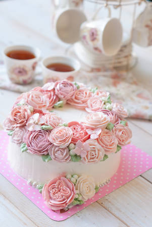 Foto de Gorgeous cake covered in roses made of butter cream icing on white wooden background - Imagen libre de derechos