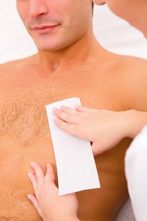 Photo pour Man waxing his chest hair - image libre de droit