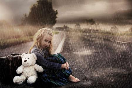 Foto de Lonely girl alone on the street on a rainy day - Imagen libre de derechos