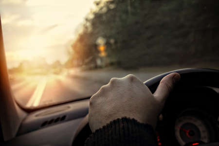 Photo pour hand on the steering wheel - the driver drives into the sunset - image libre de droit