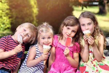 Foto de adorable children eating ice cream on holiday - Imagen libre de derechos