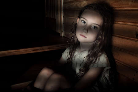 Photo for Depressed girl sitting in a dark hallway in home - Royalty Free Image