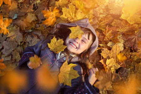 Photo for Young girl lying in colorful leaves - Royalty Free Image