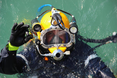 Foto de diver in the water in a diving suit and helmet ready to dive and showing sign ok - Imagen libre de derechos