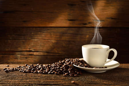 Foto de Coffee cup and coffee beans on old wooden background - Imagen libre de derechos