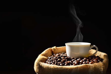 Photo for Cup of coffee with smoke and coffee beans in burlap sack - Royalty Free Image