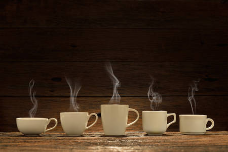 Photo pour Variety of cups of coffee with smoke on wooden background - image libre de droit