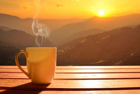 Foto de Morning cup of coffee with mountain background at sunrise - Imagen libre de derechos