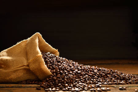 Foto de Coffee beans in burlap sack on wooden table,This photo is available with smoke - Imagen libre de derechos