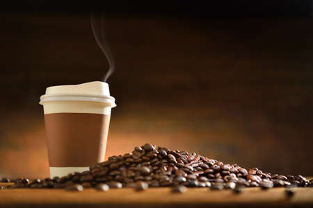 Photo pour Paper cup of coffee with smoke and coffee beans on old wooden background - image libre de droit